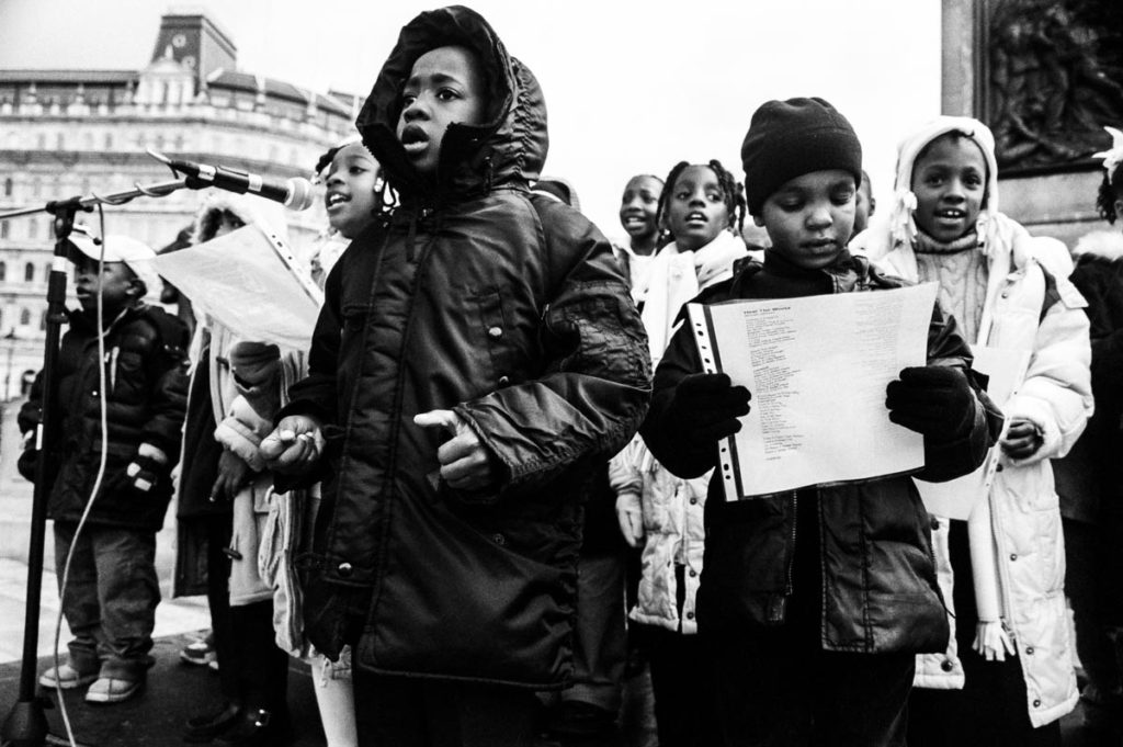 """At the end of the 2004 Million Man March in London, against the backdrop of Nelson's Column in Trafalgar Square, children from the Nation of Islam sing """"Heal the World"""" by Michael Jackson, London, England, 2004. Image copyright © Thaddeus Pope 2004."""