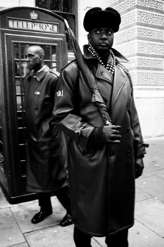 """Two members of the Nation of Islam (NOI) stand next to a British red telephone box during the """"Million Man March"""" between Parliament Square and Trafalgar Square in central London. Image copyright © Thaddeus Pope, 2006."""