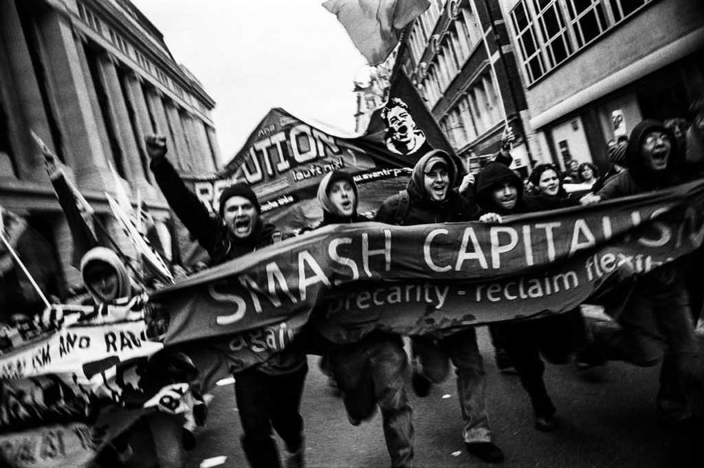 """""""Smash Capitalism"""", London, England, October 2004. Following a day of seminars, workshops and cultural events at The Third European Social Forum – an event which focused on addressing major European and global issues, with particular attention paid to coordinating efforts against the ongoing occupation of Iraq – tens of thousands of antiwar and anti-capitalist protestors held an impassioned demonstration in central London. Image copyright © Thaddeus Pope 2004."""