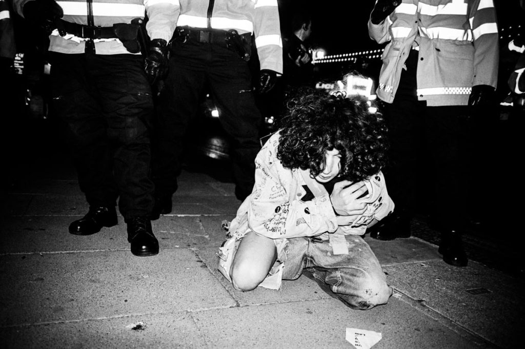 A man is injured after police clash with anti-war protestors on Brighton Seafront, England (2003). Image © Thaddeus Pope