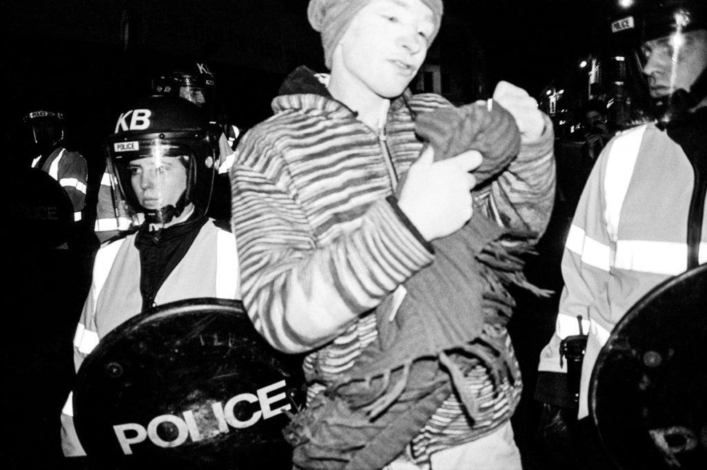 An anti-war protestor wearing white face paint dances through a line of riot police on Brighton Seafront, England (2003). Image © Thaddeus Pope