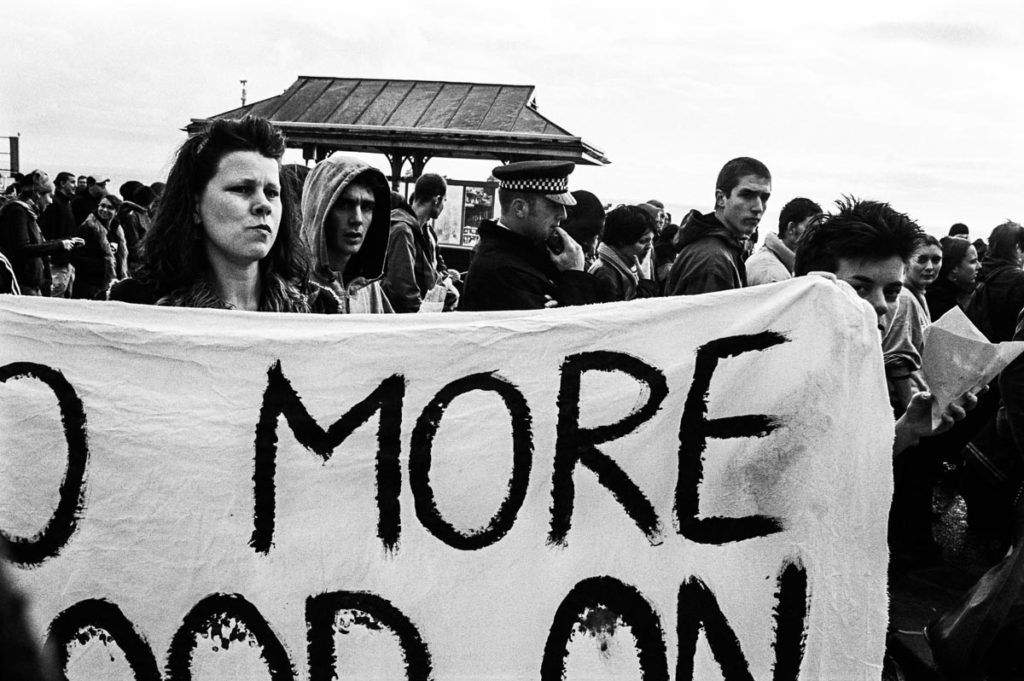 Anti-war protestors hold a banner that reads, 'NO MORE BLOOD ON BRITISH HANDS' on Brighton Seafront, England (2003). Image copyright © Thaddeus Pope
