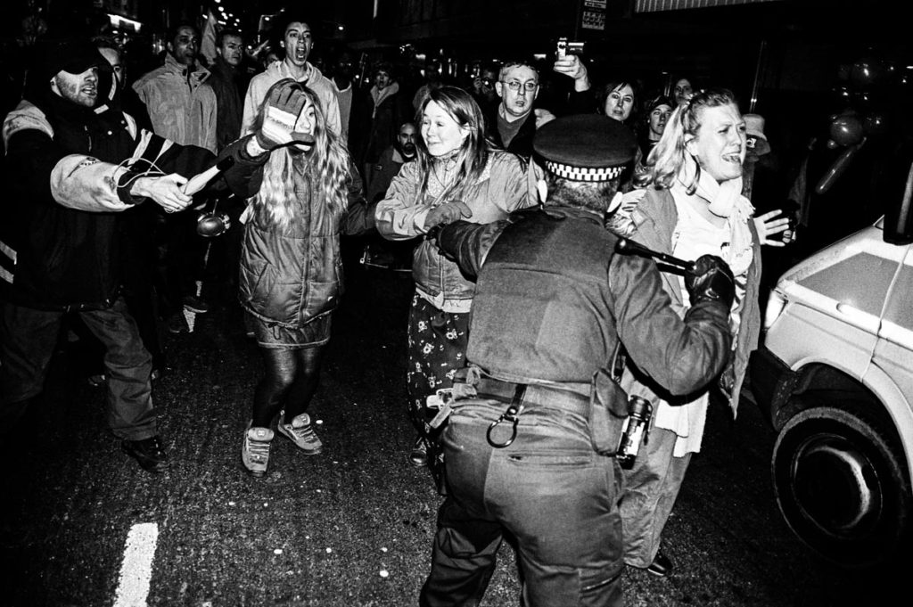 Armed with a baton, a British policeman uses force to control crowds of anti-war protestors in Brighton, England (2003). Image © Thaddeus Pope. (1/2)