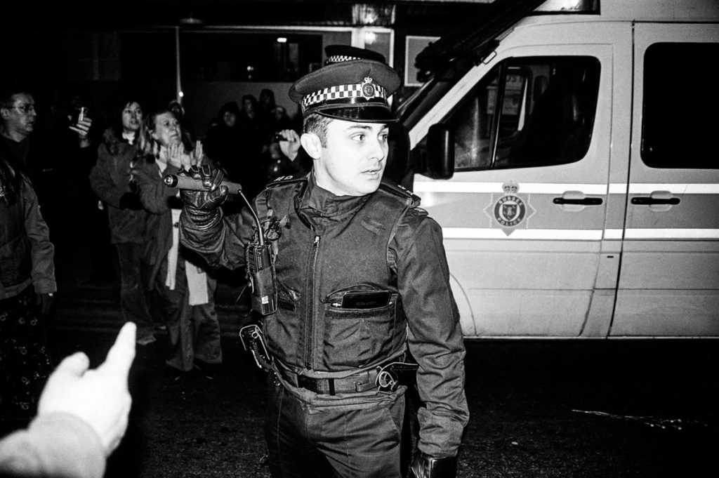 Armed with a baton, a British policeman uses force to control crowds of anti-war protestors in Brighton, England (2003). Image © Thaddeus Pope. (2/2)