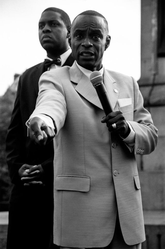 Standing on a platform in Trafalgar Square against the backdrop of Nelson's Column, minsters from the Nation of Islam address a large crowd of their followers during the Million Man March, London, England, 2004. Image copyright © Thaddeus Pope 2004.